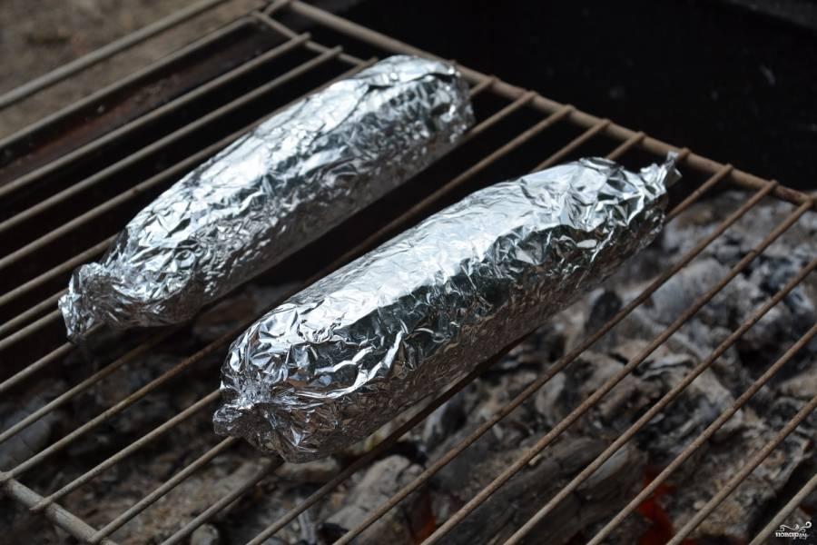Когда дрова в мангале полностью прогорели и остались одни угли, положите решетку, а на нее — кукурузу. Запекайте примерно 30 минут при условии хорошего жара. Не забывайте периодически переворачивать початки, чтобы они равномерно пропеклись. Если температура углей меньше, то и готовить стоит немного дольше.