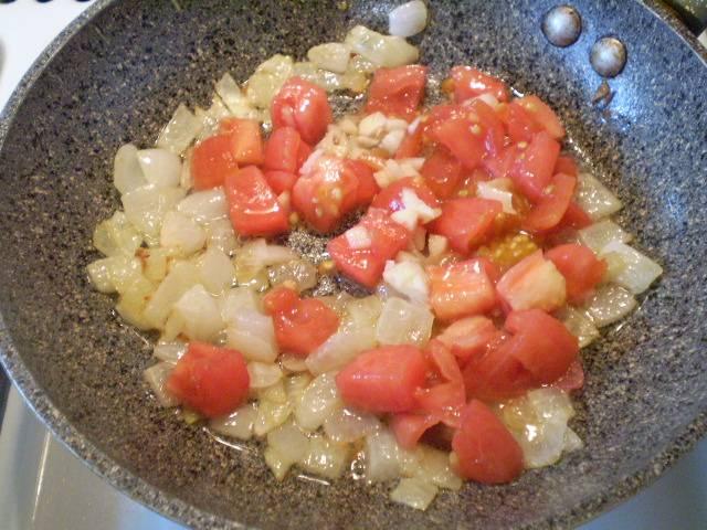 Обжарьте сначала до полуготовности лук. Добавьте помидор. Протушите пару минут.