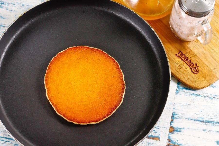 Переверните на другую сторону и обжарьте еще минуту. Таким образом обжарьте все оставшееся тесто, превращая его в ароматные блины.