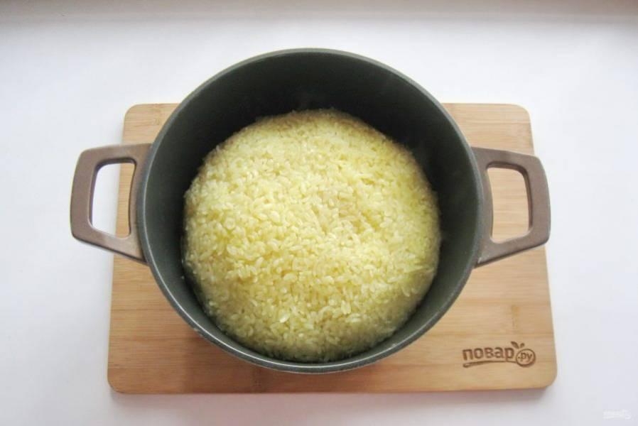 После соберите рис горкой от краев к середине казана, убавьте огонь до минимума и накройте казан крышкой. Через 20-25 минут плов будет готов.