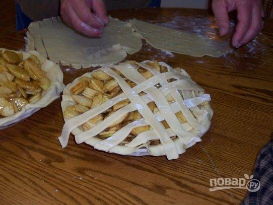 Влейте карамель на пирог, равномерно распределите по всем яблокам. Накройте пирог полосочками теста в виде решетки.