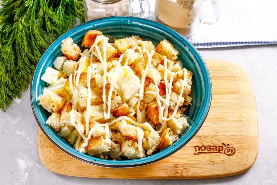 Выложите сухарики, и добавьте майонез любой жирности. Сухарики добавляйте любые, по вашему вкусу.