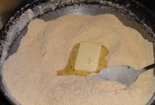 Муку со сковороды не убираем! Пока она горячая, постепенно вводим масло, кусочками порезав его. Масло будет сразу таять, размешивайте его ложкой с мукой в тот же момент.