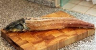 В то время, как подходит к концу процесс обработки осетрины, наливаем в большую кастрюлю воду и доводим ее до сильного кипения. В кипящую воду опускаем осетра буквально на несколько секунд и потом сразу же обдаем рыбу холодной водой. После чего с легкостью сдираем шкуру и шипы. Натираем рыбу солью и оставляем при комнатной температуре примерно на 40-60 минут, чтобы рыба дала сок. В это время займемся приготовлением соуса.