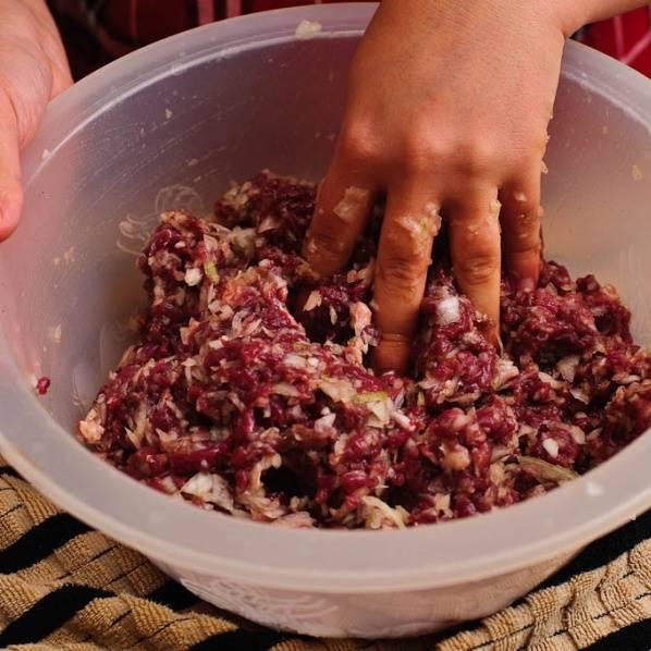 Добавить соль, черный перец и хорошо перемешать руками. Положить начинку в холодильник.