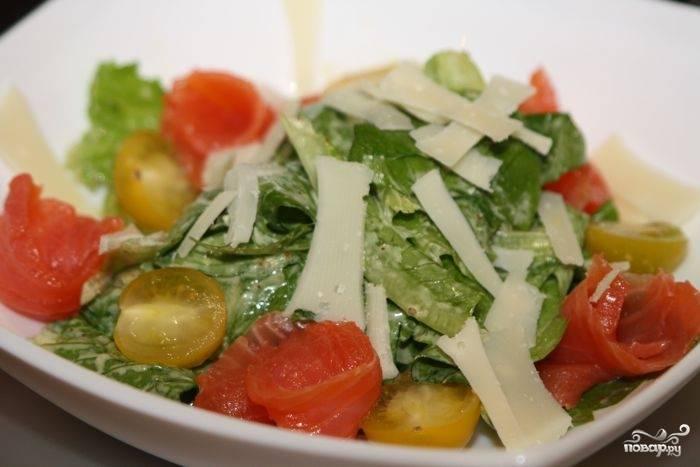 Заправить салатные листья соусом и осторожно перемешать. Выложить крутоны и рыбу, сбрызнуть оставшимся соусом. При желании украсить половинками помидоров черри. Посыпать тертым пармезаном и подать на стол!