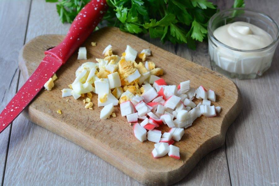 Сварите куриные яйца вкрутую, остудите и нарежьте кубиками. Размороженные крабовые палочки нарежьте кубиками.