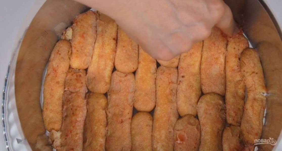 4. Печенье савоярди окуните в сироп верхней частью и выложите нижней частью на блюдо. Заполните дно формы печеньем и отправьте в холодильник. Густой йогурт соедините с сахаром и ванильным сахаром. Тщательно размешайте.