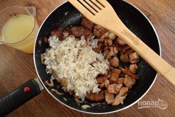Лук, чеснок измельчите и пассеруйте до мягкости на оставшемся масле. Затем добавьте паприку, рис, перемешайте и готовьте  полминуты. Добавьте горячий бульон, закройте крышкой, готовьте рис до состояния аль-денте. Теперь добавьте мясо, колбасу, соль и перец по вкусу, перемешайте.