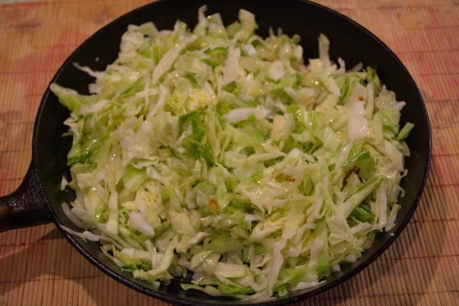Добавьте капусту, сразу перемешайте и обжарьте все вместе. Периодически помешивайте. Жарим до готовности. Посолите, поперчите.