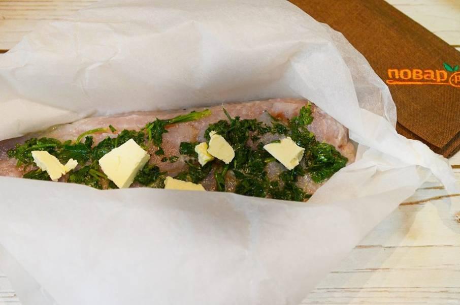 4. Сформируйте из пергамента конверт, выложите  рыбу и сверху положите кусочки масла. Запекайте в разогретой до 180 градусов духовке около 30 минут.