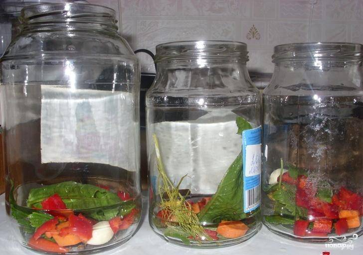 На дно банок уложить специи и порезанные овощи.