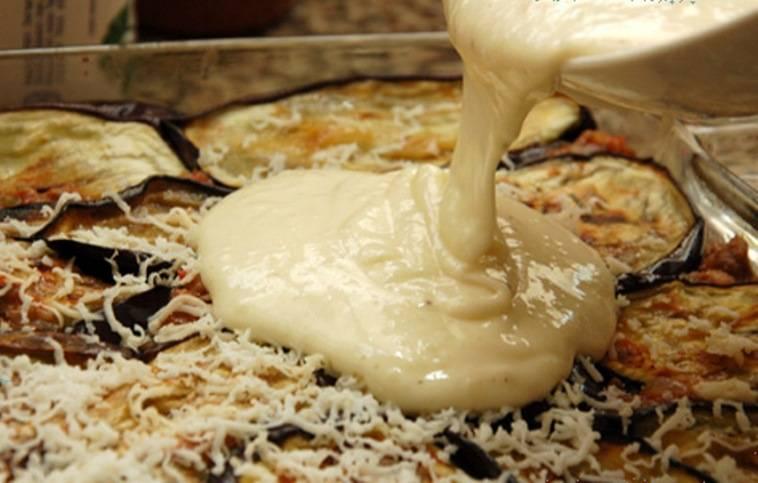 В отдельной миске взбейте желтки и оставшийся сыр. Добавьте их в соус, при этом помешивая, чтобы желтки не затвердели от температуры. Этим соусом залейте баклажаны так, чтобы он покрывал всю поверхность.