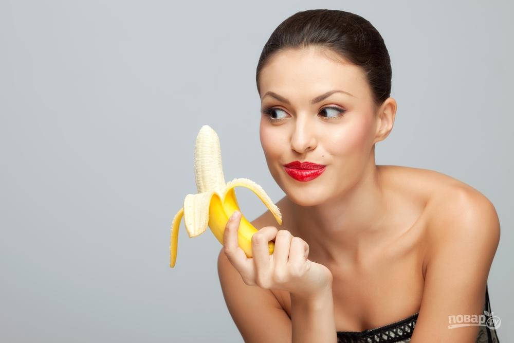Женщина кушает банан
