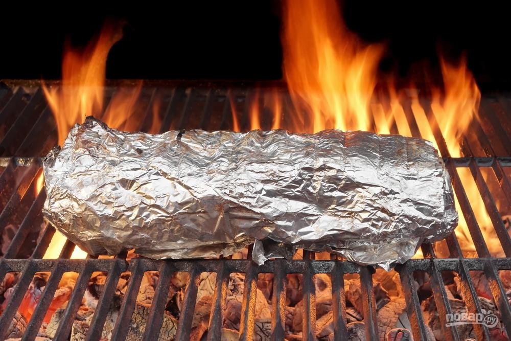 Мясо в фольге запекается на гриле