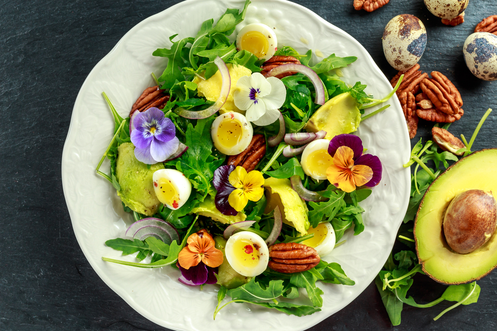 Свежий салат со съедобными цветами, зеленью, яйцами и орехами