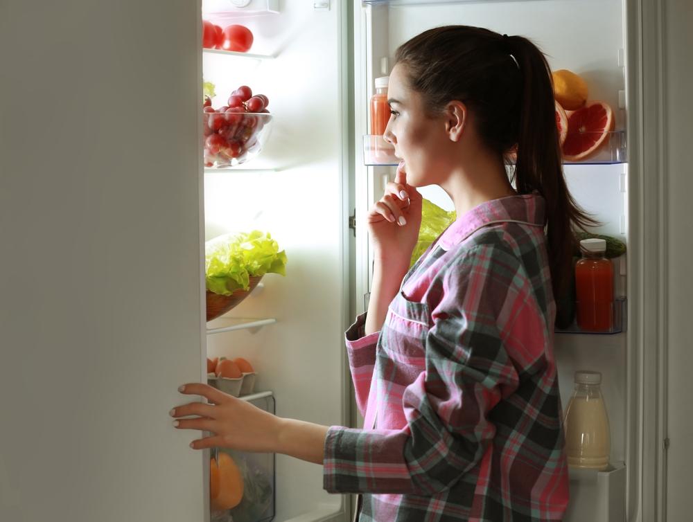 Женщина у холодильника с фруктами и овощами