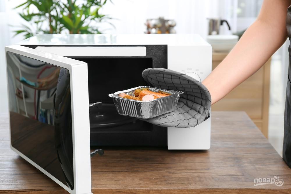 Женщина готовит картошку в микроволновке