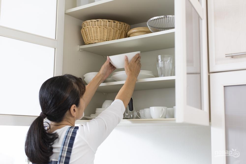 Женщина убирает посуду в кухонный шкафчик