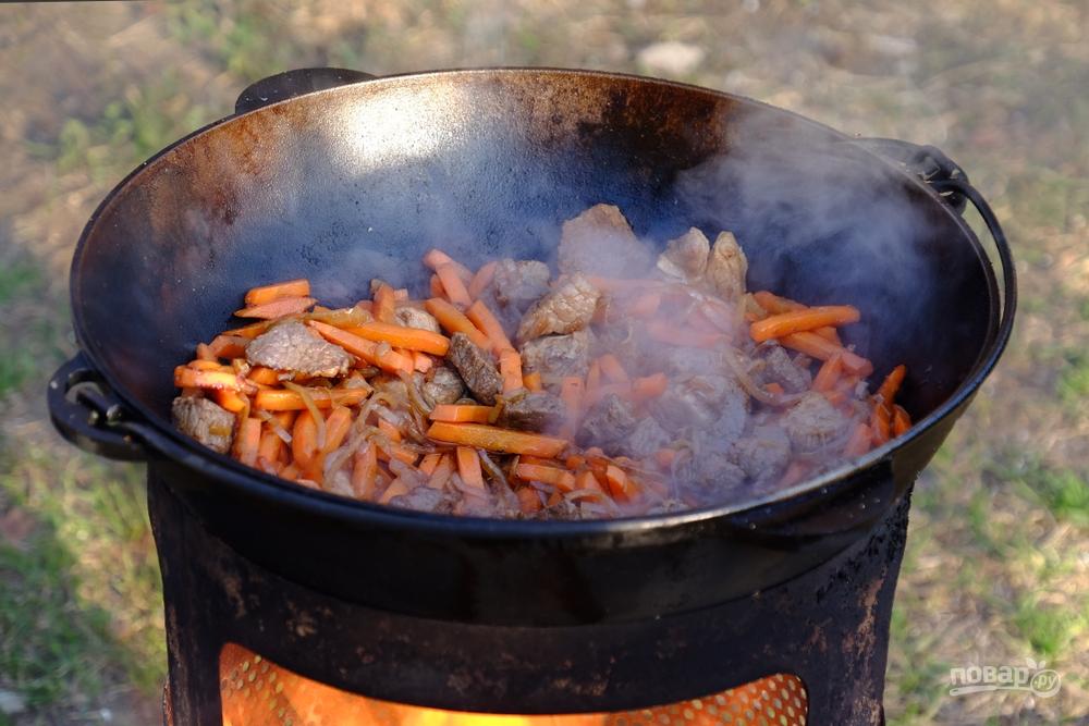 Готовим плов: в казане жарятся мясо и овощи