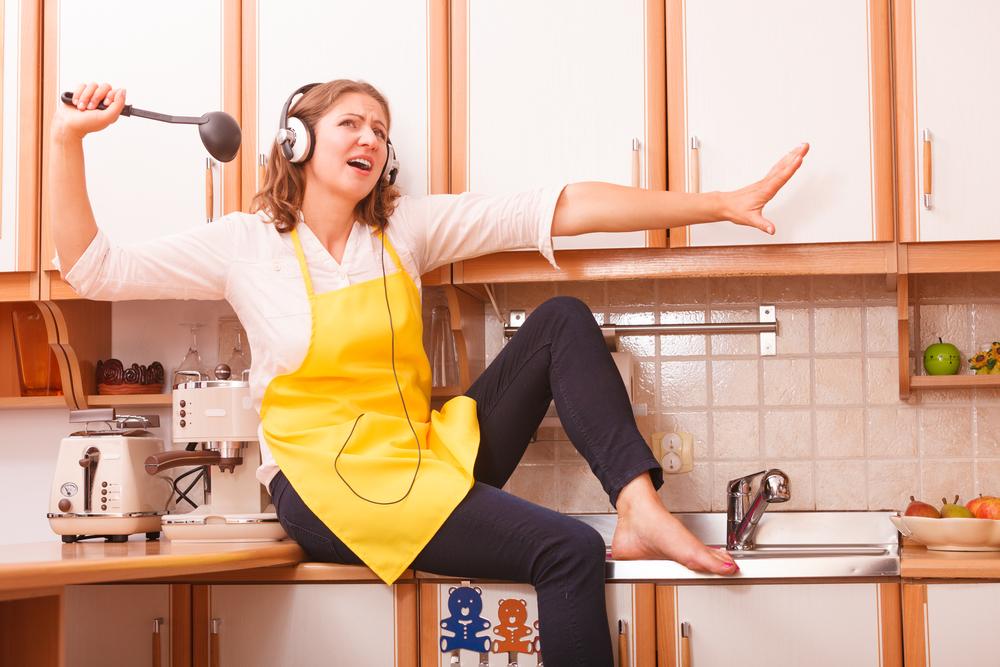 Женщина поет на кухне