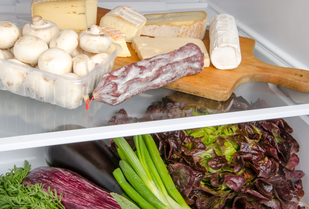 Сыр на разделочной доске в холодильнике