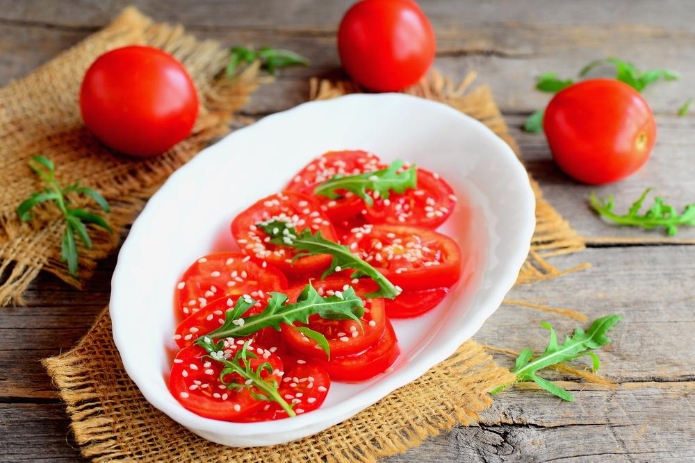Салат из помидоров и рукколы с кунжутными семенами и заправкой из растительного масла с уксусом