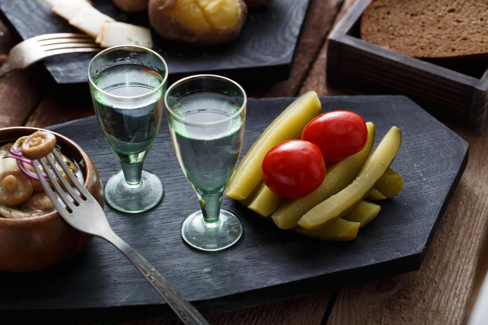 Водка с закуской - маринованными огурчиками, помидорами и солеными грибами